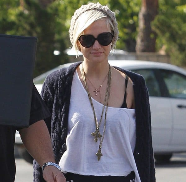 Ashlee Simpson wearing a layered cross pendant necklace