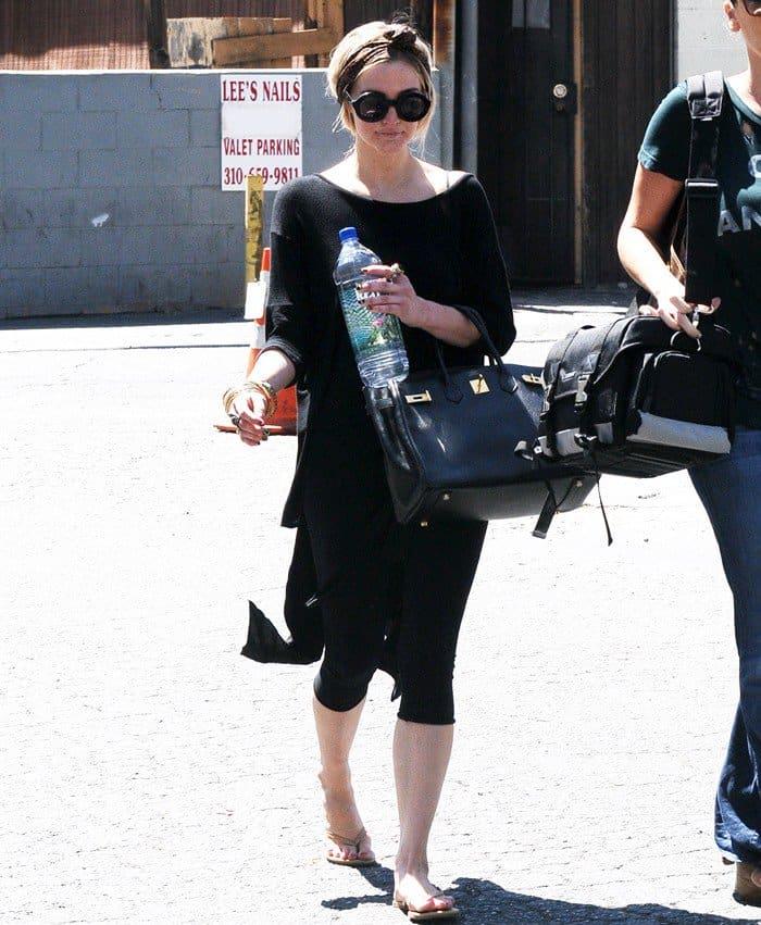 A pile of bangles making Ashlee Simpson's all-black attire shimmer as she leaves the dance studio