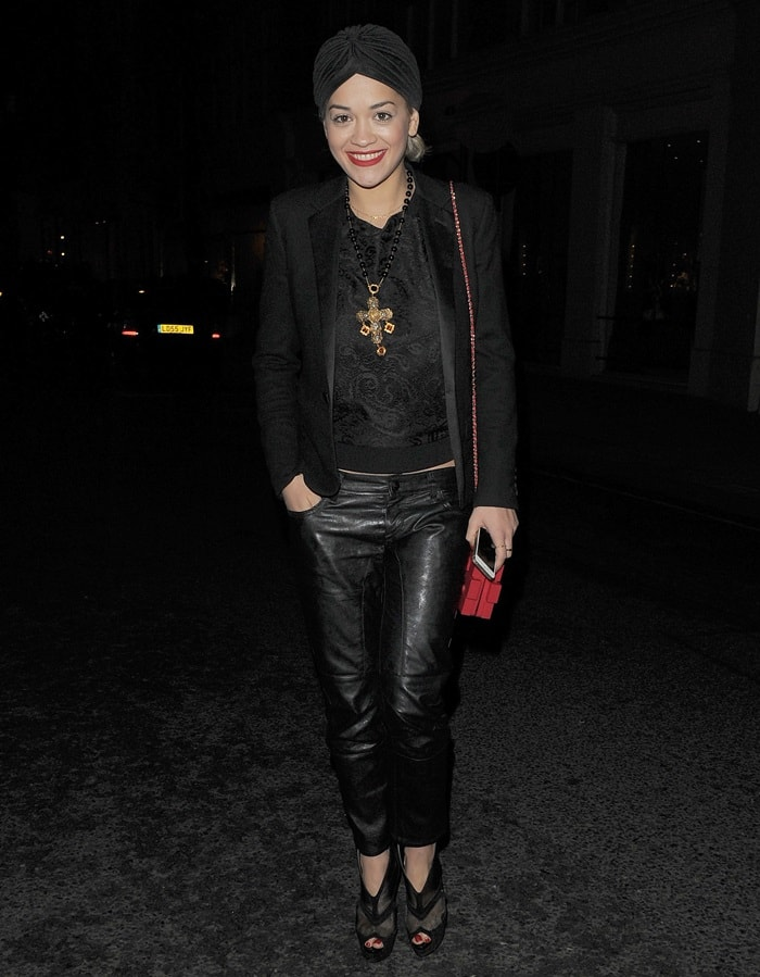 Rita Ora sported an all black ensemble that was punctuated by a bold rosary necklace with an intricately styled golden cross