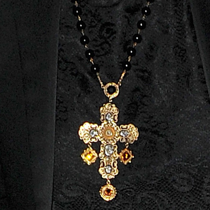 Rita Ora star sported an all black ensemble that was punctuated by a bold rosary necklace with an intricately styled golden cross