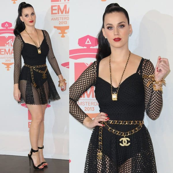 Katy Perry wearing a gold-and-black-leather Chanel chain belt, a Chanel No. 5 long necklace, and a Chanel charm bracelet with her racy black mesh dress