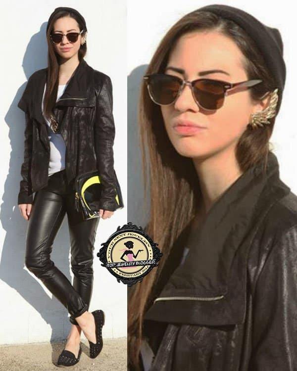 Christy rocks a black jacket over a white top, sleek black pants, black studded shoes, and a beanie