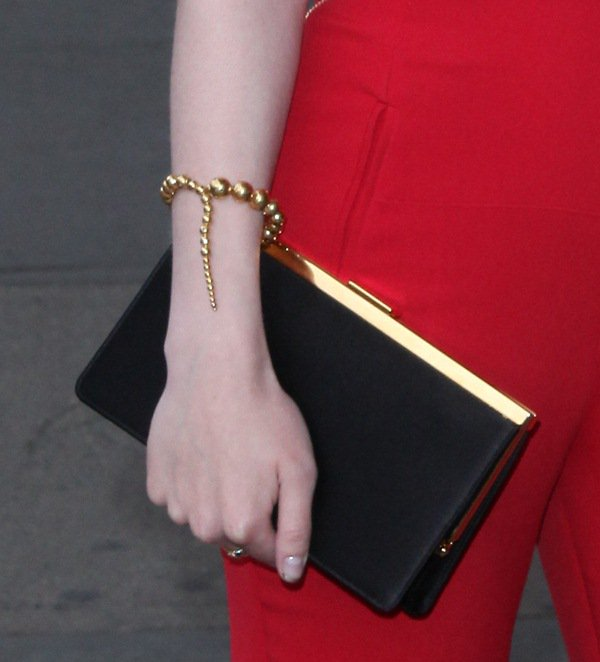 Dakota Fanning totes a black satin clutch