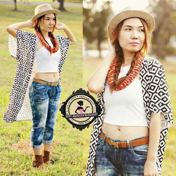 Julie styled a chic necklace with distressed boyfriend jeans, a printed cape, and a fedora