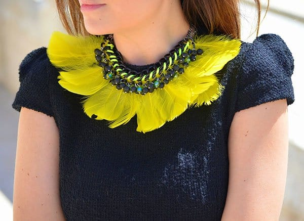 Patricia's vivid yellow feather necklace featuring iridescent green crystals and black stones