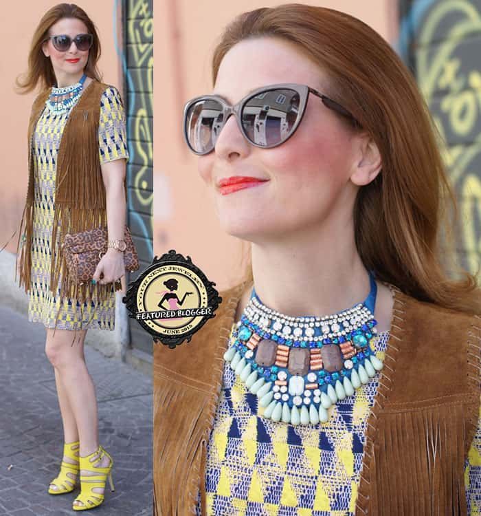 Valentina wears a brown fringed vest with an intricately embellished statement bib necklace