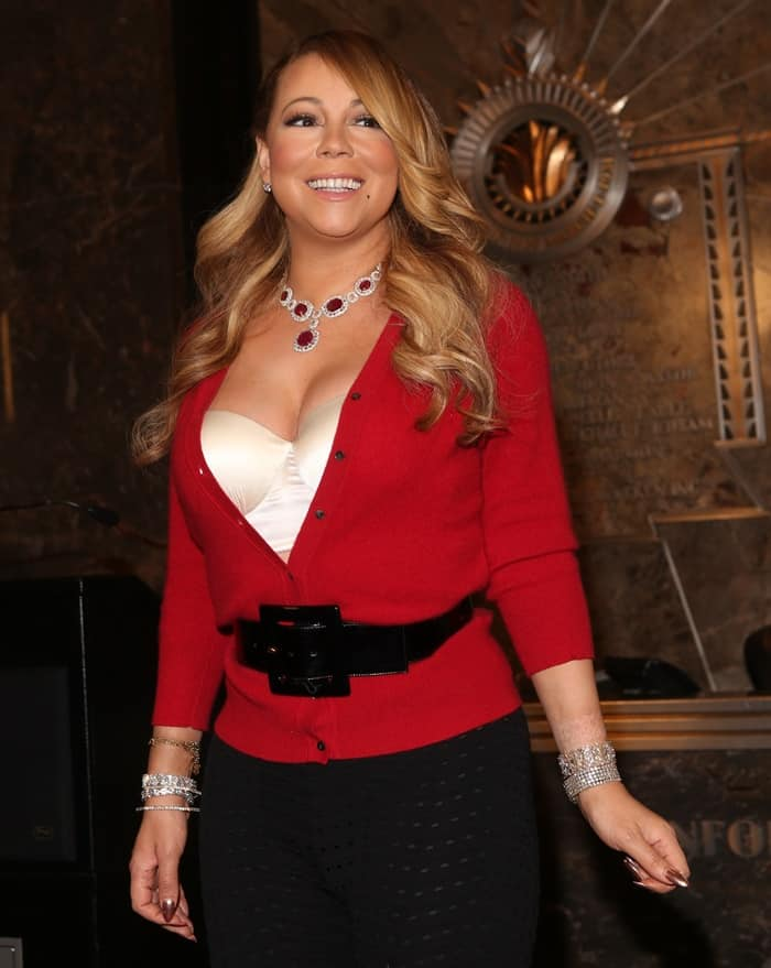 Mariah Carey wore a festive red cardigan and black tights styled with a thick leather belt