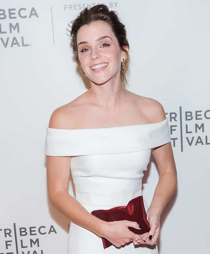 Emma Watson added some color to her look with a red velvet clutch