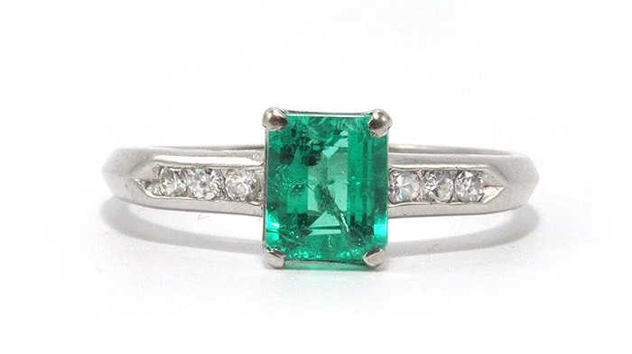 A 0.93-carat bright green Colombian emerald glows between a row of six diamonds set in a platinum band
