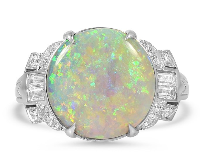 Unique retro-era Felita ring holds a round opal cabochon surrounded by a total of 0.60-carat 20 brilliant and baguette diamonds
