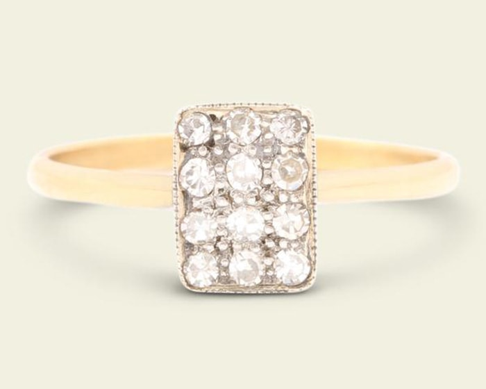 An early Deco engagement ring fashioned in 18k yellow gold band with platinum-topped diamond-studded rectangular face