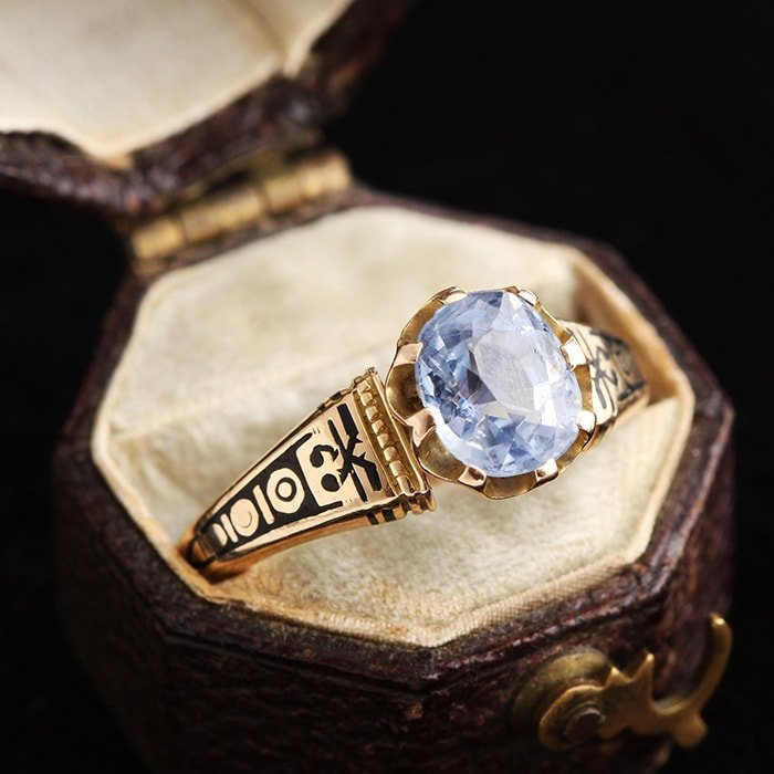 Intricately designed Victorian engagement ring featuring 1.41-carat pale sapphire set in 14k gold band with black enamel detailing