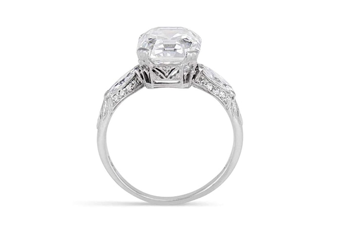 A vintage engagement ring featuring a 4.77-carat elongated asscher-cut diamond with single, marquise-cut diamond shoulders in a platinum band