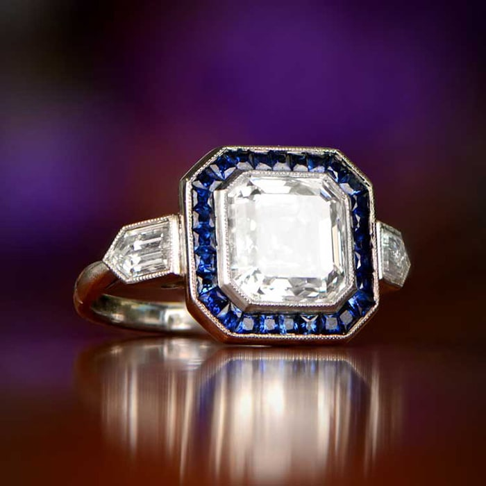 The Crawford ring features a 3.26-carat antique Asscher cut diamond surrounded by French cut Ceylon sapphires with two straight-lined bullet-shaped diamonds on each shoulder