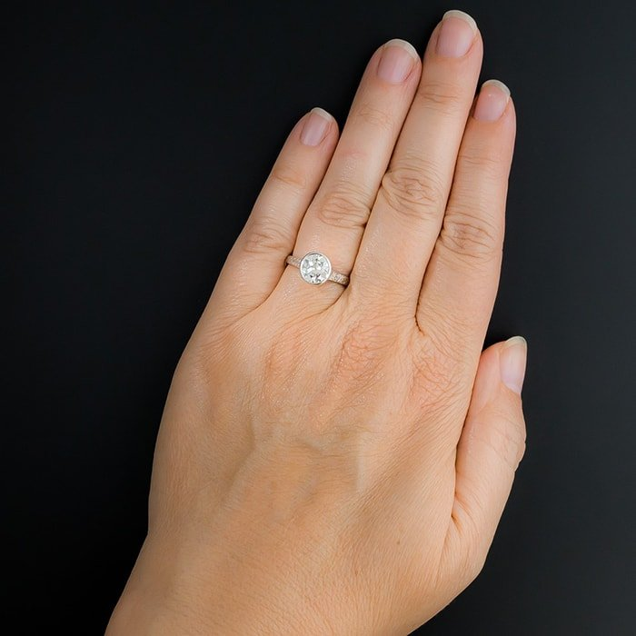 A 1.65-carat bright white European cut diamond sparkles from within the platinum bezel and refined Edwardian solitaire mounting