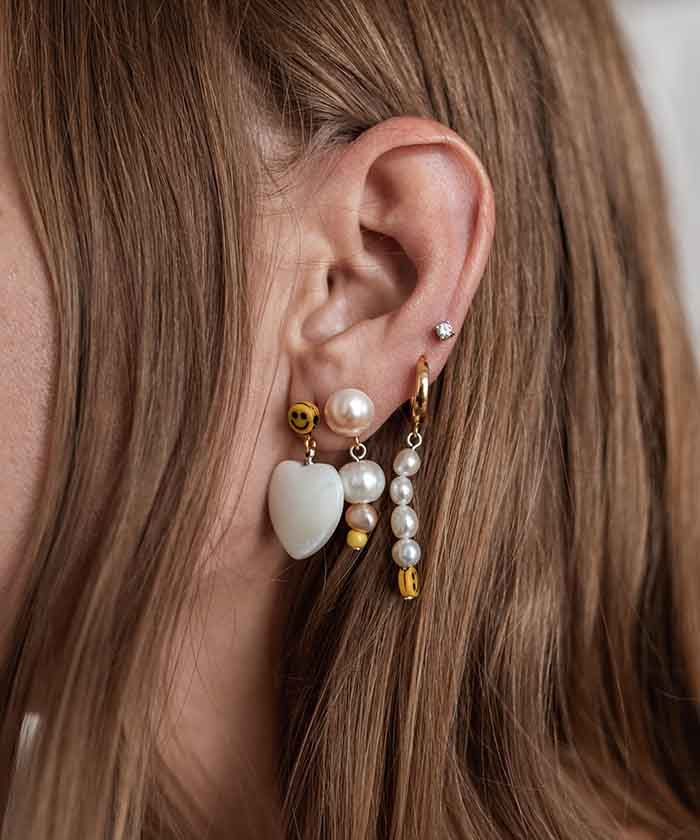 Complete an ear party with the Smilie Dude Earring set featuring gold-plated silver hoops, sweet water pearls, glass pearls, and a smiley