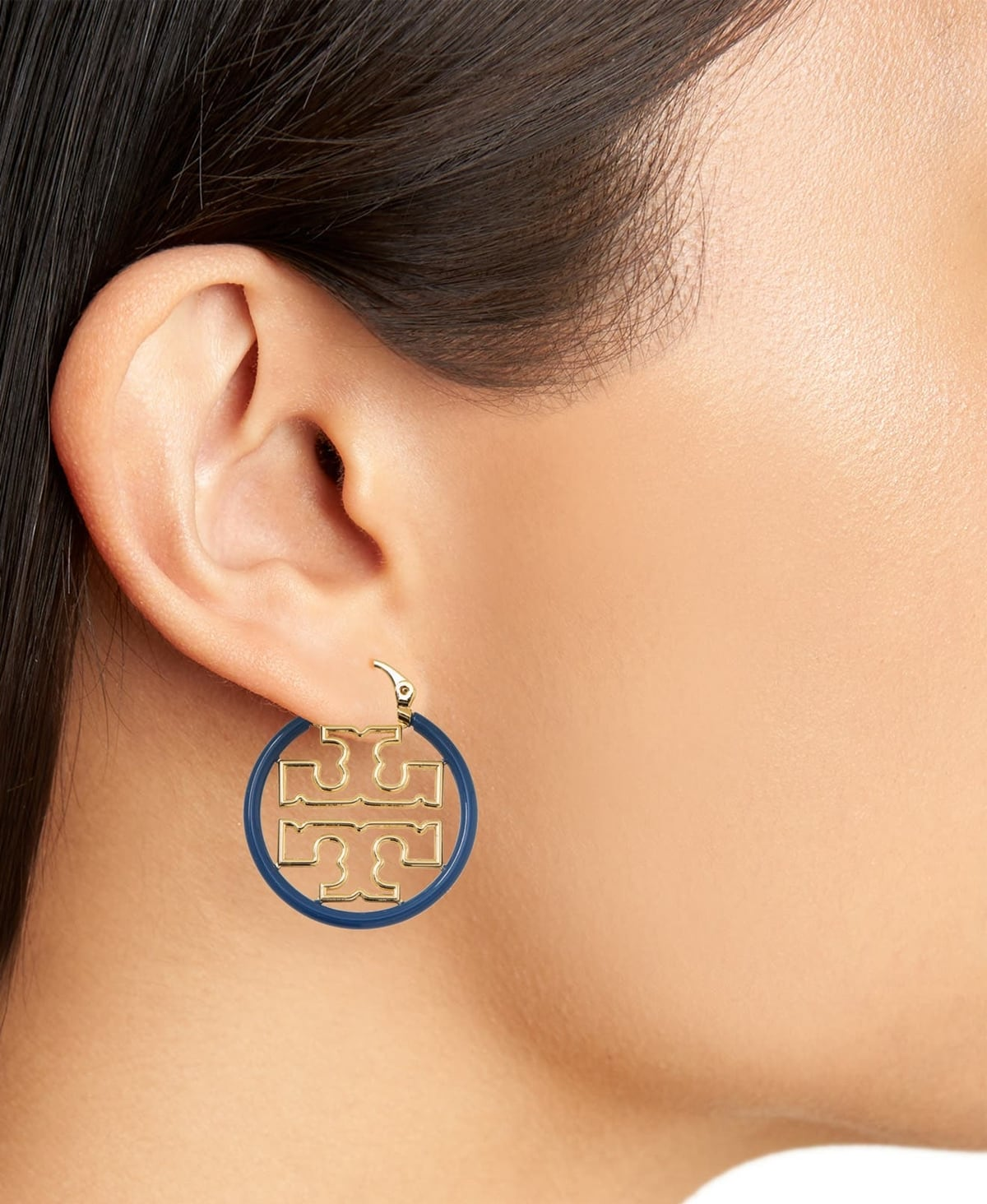 Smooth enamel surrounds glinting double-T logos in these small blue and gold hoop earrings from Tory Burch